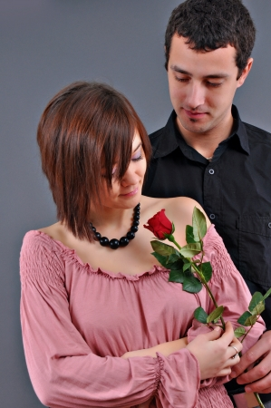 happy beautiful teenage couple, a boy giving a rose to his girlfriend photo