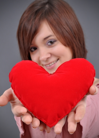 The beautiful young woman holds in hands a red heart on a grey background  Selective focus on heart   photo