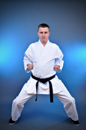Young sporty karate man doing special exercise on gray background  Stock Photo