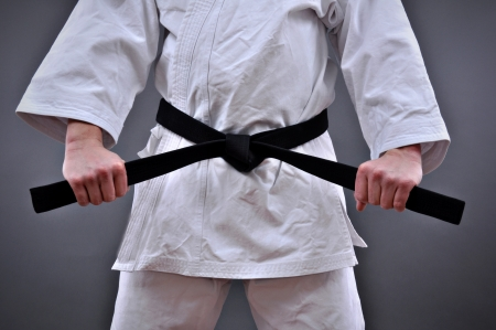Man in martial arts uniform holding his black belt with both hands  Stock Photo