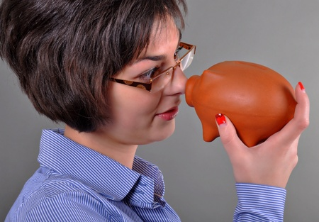Young woman trying to get money from her piggy bank photo