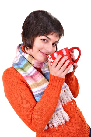 Pretty smiling girl in winter clothes with a red cup of hot drink. photo