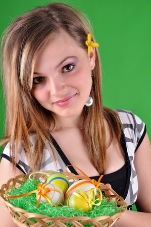 Young beautiful girl with basket and easter eggs in her hand  photo