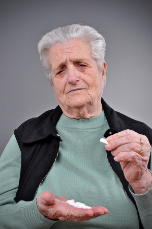 A senior woman with pills in her hand  photo