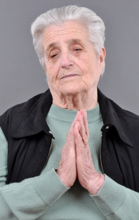 Old, attractive Caucasian woman praying Stock Photo - 16326892