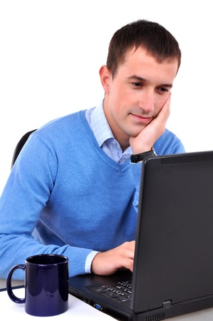 chat online: Young man reading on laptop, drinking tea or coffee Stock Photo