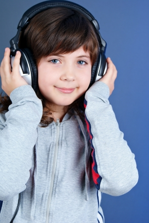 Cute little girl with earphones isolated on blue