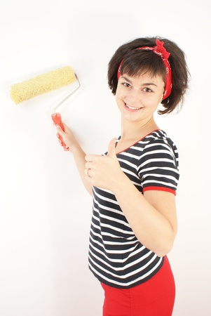 Pretty young woman with painting roller isolated on white