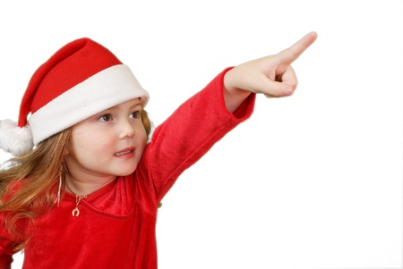 Little girl in Christmas hat pointing, isolated on white  photo