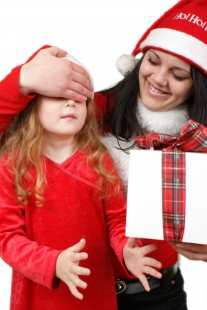 Little girl friend gives a holiday gift in red box with white ribbon.  photo