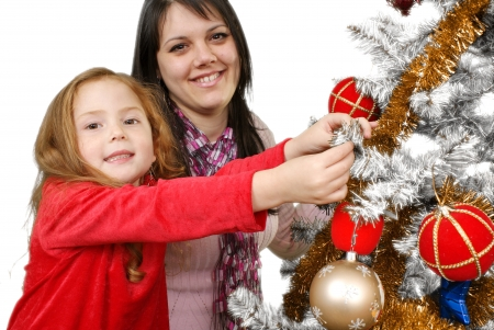 Two Young happy woman decorating the Christmas tree  Studio shot  White background  photo