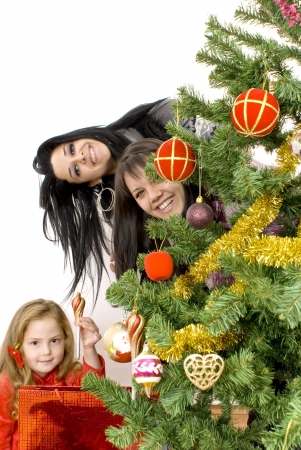 Three young happy women decorating the Christmas tree  Studio shot  White background  photo