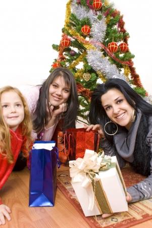 Three young happy womenwhit gift box. Studio shot. White background  photo