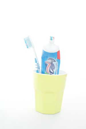 Toothbrush and toothpaste in cup, isolated on white background  photo