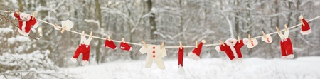 affixed: Red santa claus clothes drying in the open air hanging on clothes line affixed with wooden pegs