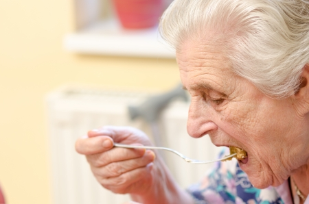 mature old generation: Happy old gray-haired woman eating