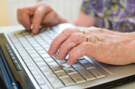 The senior hand presses the laptop keyboard button  Stock Photo