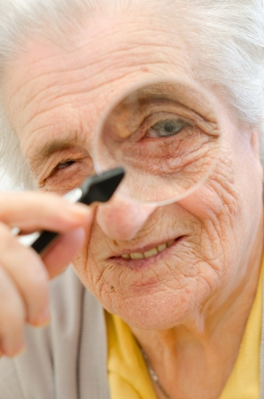 Happy old gray-haired woman with magnifier Stock Photo - 16306321