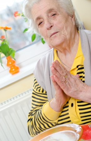 Senior woman folded her hands in prayer photo