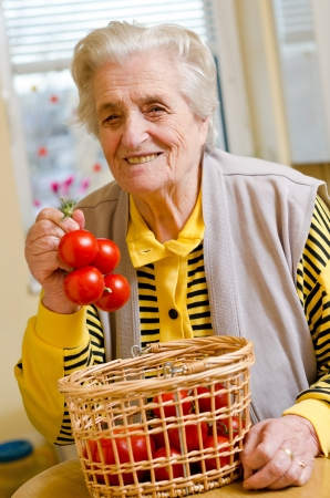 Happy old gray-haired woman with tomato Stock Photo