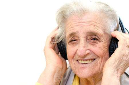 portrait of a senior woman listening to music on white background
