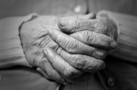 Closeup of an old womans hands joined , focus on hands