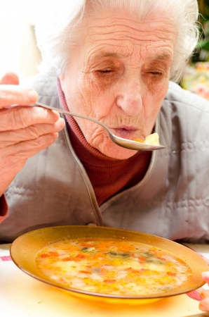 congenial: Happy old gray-haired woman eating
