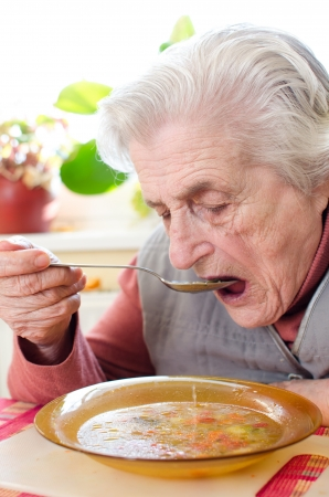 congenial: Happy old gray-haired woman eating soup Stock Photo