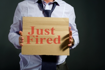 fired employee holding just fired sign in hand photo