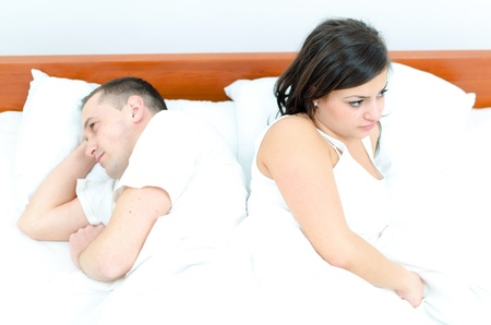 A young couple in bed having problems photo