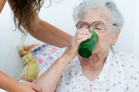 elderly woman drinking water from a glass helpd by her daughter Stock Photo