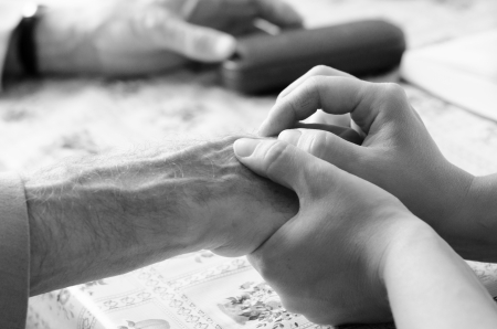 Young woman hand touches and holds an old mans wrinkled hands photo