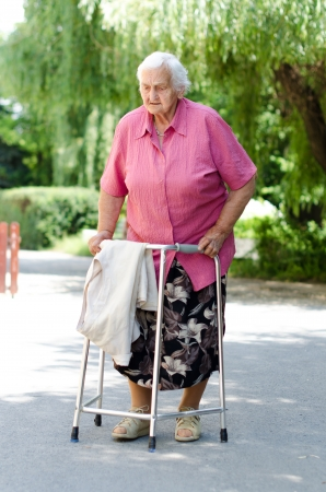 An elderly woman standing with her walker in nature Stock Photo