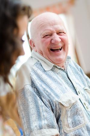 Gelukkig senior man zit binnen en laughting Stockfoto