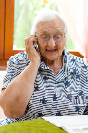 residental care: Senior Woman Dialling Number On Mobile Phone Sitting In Chair  Stock Photo
