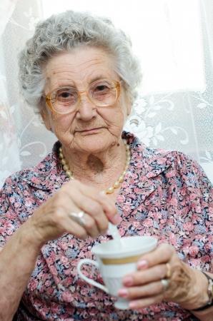 Old Woman Enjoying Cup Of Tea photo