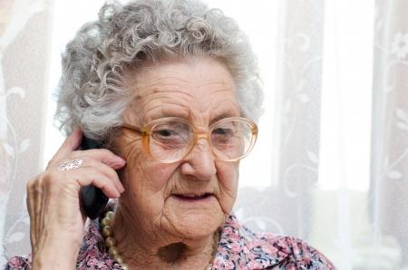 mujeres ancianas: Superior de la mujer hablando por tel�fono m�vil, sentado en la silla Foto de archivo