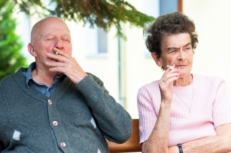 Happy old couple having a cigarette