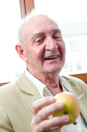Closeup profile on a smiling old man with apple