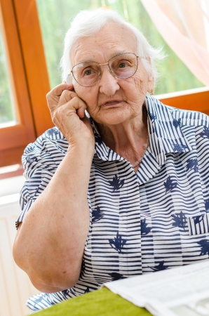 residental care: Senior Woman Dialling Number On Mobile Phone Sitting In Chair