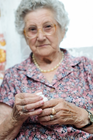 Portrait of a senior woman taking pill photo