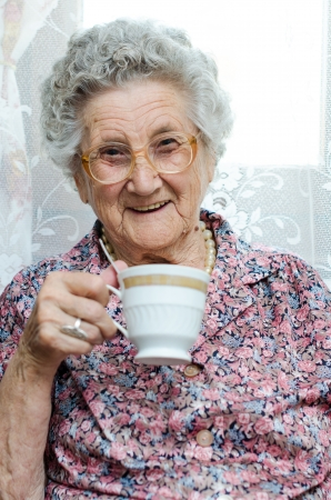 Senior Woman Enjoying Cup Of Tea At Home photo