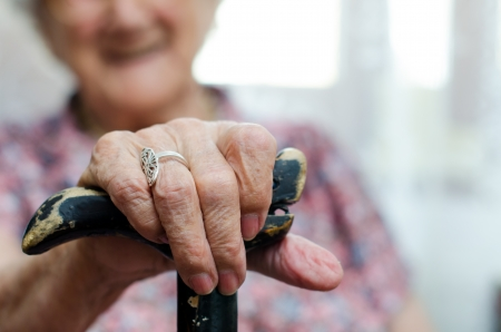 Hands of senior woman sitting in chair holding walking stick Stock Photo