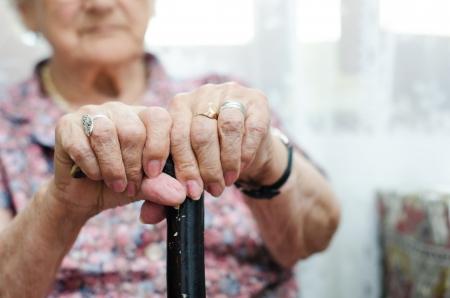 old dame: Due mani di donna senior seduta in poltrona in possesso di bastone da passeggio