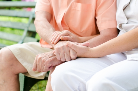 Young female hand holding an old mans hand.