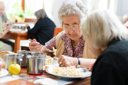 mature old generation: senior woman eating her lunch at home