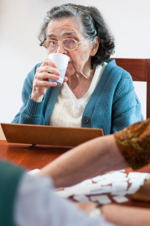 rummy: Senior drinking water and playing rummy