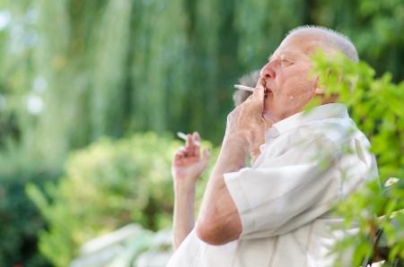 Senior man and woman smoking outdoor photo