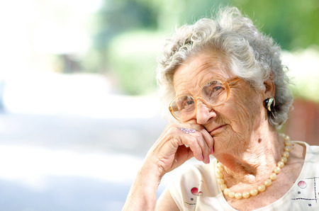 happy old people: Portrait of the smiling elderly woman, sitting outdoor  Stock Photo