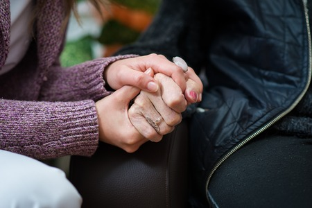 Young nurse holds the old woman hands photo